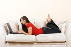 Donna con un computer portatile su un salotto fotografie stock libere da diritti