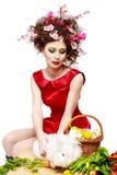Donna con un concetto di pasqua della molla del coniglietto, delle uova e dei fiori Immagine Stock Libera da Diritti