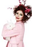 Donna con un concetto di pasqua della molla del coniglietto, delle uova e dei fiori Fotografie Stock