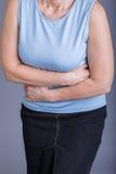 Donna con un dolore di stomaco Immagine Stock