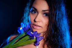 Donna con un fiore blu dell'iride Fotografia Stock Libera da Diritti