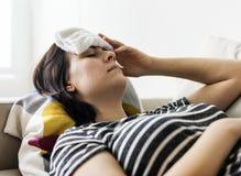Donna con un freddo e una febbre alta Immagini Stock Libere da Diritti
