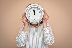 Donna con un grande orologio immagini stock
