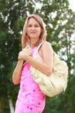 Donna con un libro a disposizione e una borsa Fotografia Stock Libera da Diritti
