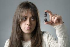 Donna con un pezzo degli scacchi fotografia stock