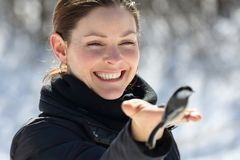 Donna con un piccolo uccello durante l'inverno immagini stock libere da diritti