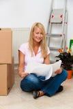 Donna con un programma nel nuovo movimento dell'appartamento. Fotografia Stock Libera da Diritti
