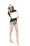 Donna con un segno in cappello di natale bianco Fotografie Stock Libere da Diritti