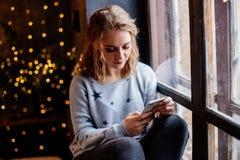 Donna con un telefono dalla finestra fotografie stock
