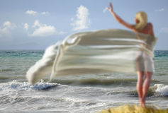 Donna con un tessuto su una spiaggia Fotografia Stock Libera da Diritti
