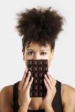 Donna con una barra di cioccolato immagine stock