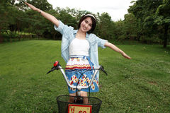 Donna con una bici all'aperto che sorride Fotografia Stock