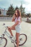 Donna con una bicicletta, estate nella citt? La maglietta rosa e la gonna bianca mette Capelli lunghi Chiamate dal telefono, onli immagini stock libere da diritti