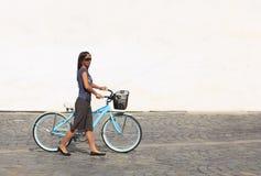 Donna con una bicicletta in una città Immagini Stock Libere da Diritti