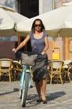 Donna con una bicicletta in una città fotografia stock