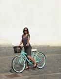 Donna con una bicicletta in una città Fotografia Stock Libera da Diritti