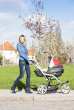 Donna con una carrozzina Fotografie Stock Libere da Diritti