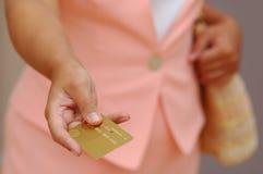 Donna con una carta di credito dell'oro Immagini Stock