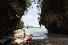 Donna con una condizione della pagaia accanto al kajak del mare alla spiaggia isolata in Krabi, Tailandia immagini stock