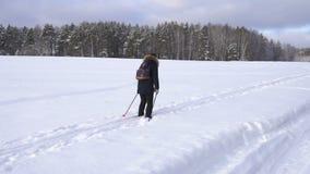 Donna con una corsa con gli sci dello zaino nella campagna nell'inverno