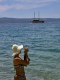 Donna con una macchina fotografica in mare fotografia stock