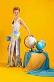 Donna con una mappa ed i globi di mondo Immagini Stock