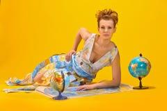 Donna con una mappa ed i globi di mondo Fotografia Stock