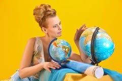Donna con una mappa ed i globi di mondo Immagine Stock