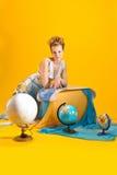 Donna con una mappa ed i globi di mondo Fotografie Stock Libere da Diritti