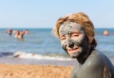 Donna con una maschera del fango sul suo fronte contro il mare Fotografia Stock