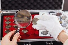 Donna con una moneta di oro e della lente d'ingrandimento nella mano Immagine Stock