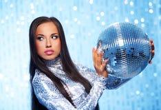 donna con una sfera della discoteca sopra priorità bassa astratta Immagine Stock