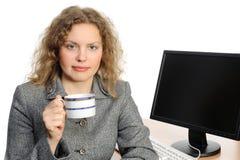 Donna con una tazza davanti al suo calcolatore fotografia stock libera da diritti