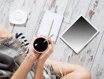 Donna con una tazza di caffè, un blocco note e una compressa Fotografia Stock