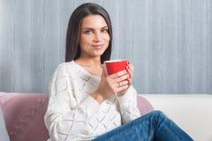 Donna con una tazza rossa in sue mani, sedute sullo strato, sguardo di sorrisi del sofà alla macchina fotografica Fotografia Stock Libera da Diritti