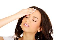 Donna con una testa della holding di emicrania Fotografie Stock Libere da Diritti