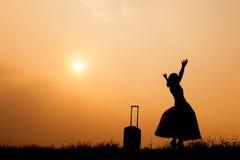 Donna con una valigia su un prato alla siluetta di tramonto Immagini Stock