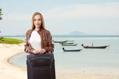 Donna con una valigia sulla spiaggia immagini stock libere da diritti