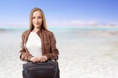 Donna con una valigia sulla spiaggia fotografia stock