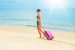 Donna con una valigia sulla spiaggia Immagine Stock Libera da Diritti