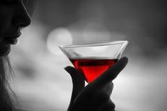 Donna con vetro della bevanda alcolica rossa Fotografie Stock