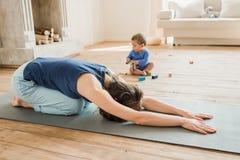 Donna con yoga di pratica del neonato a casa Donna nella posizione del ` s del bambino Fotografie Stock Libere da Diritti