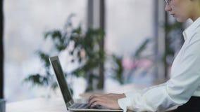 Donna concentrata che lavora fuori orario al computer portatile all'ufficio, femmina laboriosa archivi video
