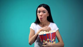 Donna concentrata che mastica popcorn e che guarda film emozionante in cinema, concetto immagine stock libera da diritti