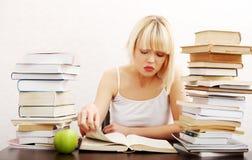 Donna concentrata che si siede con la pila di libri Immagini Stock Libere da Diritti