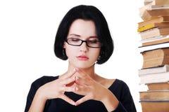 Donna concentrata che si siede con la pila di libri Fotografia Stock Libera da Diritti