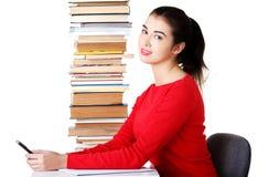 Donna concentrata che si siede con la pila di libri Immagini Stock