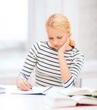 Donna concentrata che studia nell'istituto universitario Immagine Stock