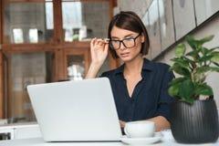 Donna concentrata in occhiali che funzionano con il computer portatile Immagine Stock Libera da Diritti