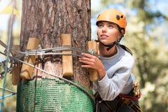 Donna concentrata seria che si nasconde dietro un albero Fotografie Stock